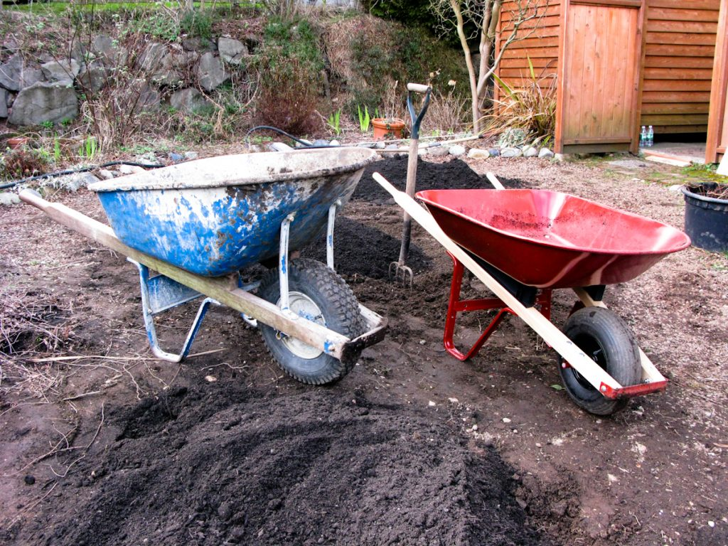 "My cute dad, Jerry, helped me work on the raised beds.  Working with my dad, I still feel like a little girl.  Here's his contractor's wheelbarrow alongside my beloved little orange one.  He said, ""Make sure you point the wheelbarrow the way you want to go before you fill it"